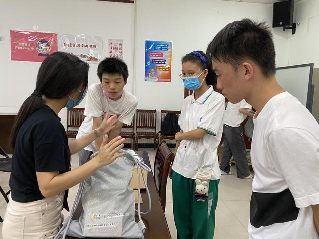 新浪广东桔子公益志愿者服务队将800份物资进行验收、分拣、装袋,志愿者在老师指导下进行工作。