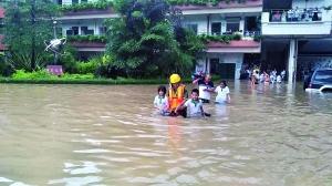 白云区永兴小学因暴雨学生被困,消防官兵手牵手,将学生带到安全地带。通讯员供图