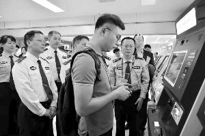 """一名办理出入境证件的市民正在使用银联""""云闪付""""。信息时报记者 陈引 摄"""