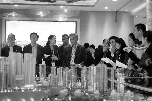 图为嘉宾在亚运城听售楼小姐讲解沙盘。 信息时报记者 郭柯堂 摄