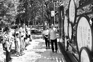 解说员在公园故事栏前给游客讲解古代好家风的故事。信息时报记者 陈引 摄