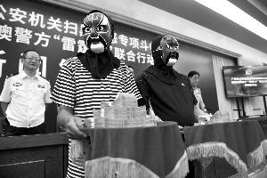昨日,两名戴着面具的市民领到共30万元的举报涉黑涉恶的奖金。   信息时报记者   陈引 摄
