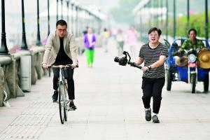 昨天下午,江边,两位正在拍摄的年轻人。短袖与外套同框。信息时报记者 康健 摄