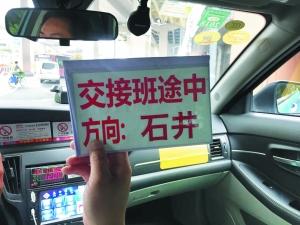 """▲新型""""交接班标识牌"""",打车时能清晰看到出租车目的地,以确定是否要招手停车。信息时报记者 康健 摄"""