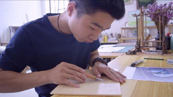 陈博在进行版画制作的雕刻环节