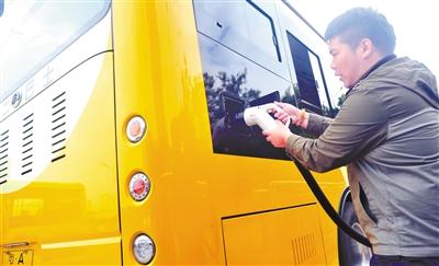 工作人员为电动公交汽车充电。(资料图片) 广州日报全媒体记者廖雪明 摄