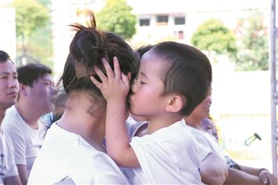 """在广州的一个""""关爱留守儿童""""主题的活动现场,孩子深情地亲吻母亲。(资料图片) 广州日报全媒体记者陈忧子 摄"""