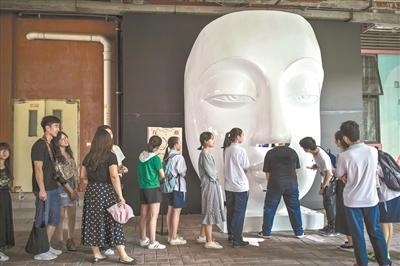 观众钻进人脸雕塑的鼻孔互动。