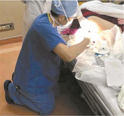 曾医生跪地为病人做手术。吴德庆摄