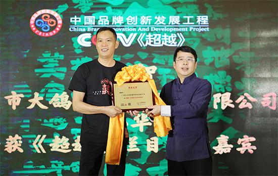 """大鸽饭入选""""中国品牌创新发展工程"""",央视主持人阿丘(右)为大鸽饭创始人黄小华(左)授牌"""