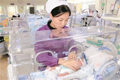 医护人员正在细心呵护早产三胞胎。