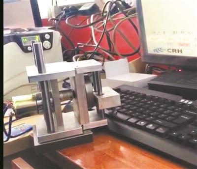 在查获现场,代售点电脑旁的一台机器人通过敲击电脑键盘抢票。