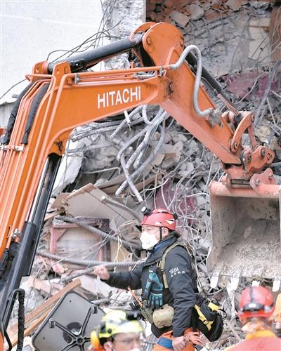 2月7日,救援人员在一处倒塌建筑前救援。新华社发
