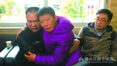 曾利信(中)与父亲见面后紧紧地拥在一起。/佛山日报记者唐格桢摄