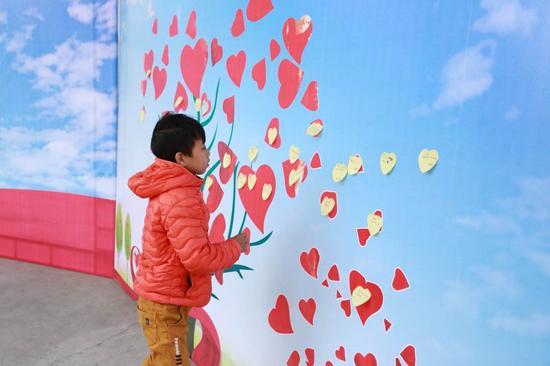 孩子们把愿望写在便利贴上,贴到许愿树上
