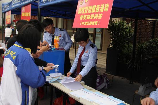 青少年喧闹到场税收知识问答活动,两名中学生用手机查阅税收知识