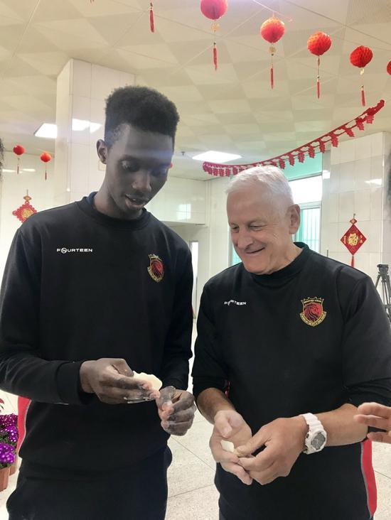 教练和球员合力包饺子。