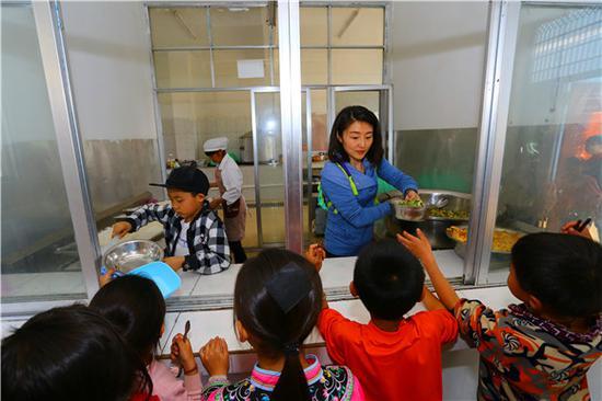 捐赠人为学生打饭