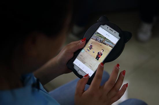 周艳看着手机里的孩子照片