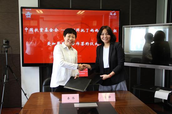 中国扶贫基金会助理秘书长秦伟(左)与东方风行传媒集团副总裁赵静(右)签署《战略合作协议》