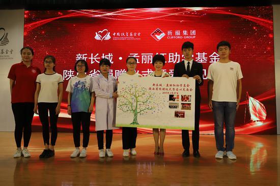 7所高校学生代表向孟丽红女士赠送全体学生签字指纹树