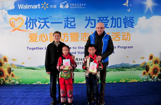 中国扶贫基金会七届理事会副理事长江绍高(左一)、沃尔玛全球执行副总裁、沃尔玛加拿大及亚洲区首席执行官岳明德(右一)为月湖小学学生代表带来营养知识手册。