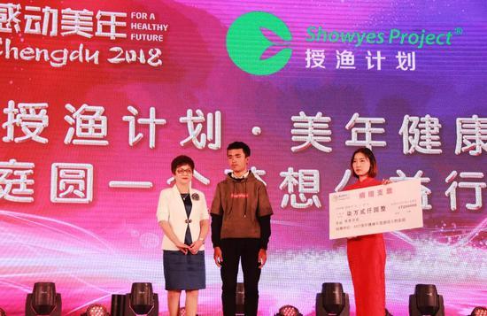 感动人物家庭代表邵明华向授渔学生代表捐赠善款