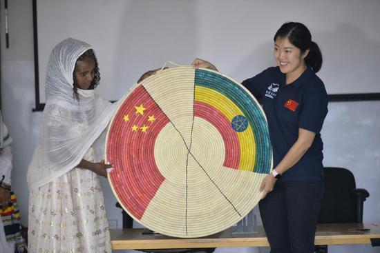 图为妇女代表向中地海外和中国扶贫基金会赠送两国国旗的篮子
