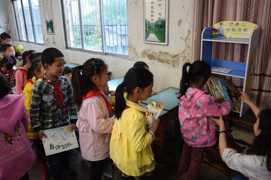 重庆万州河口完全小学的孩子们排队归还叶柏公益捐赠的绘本