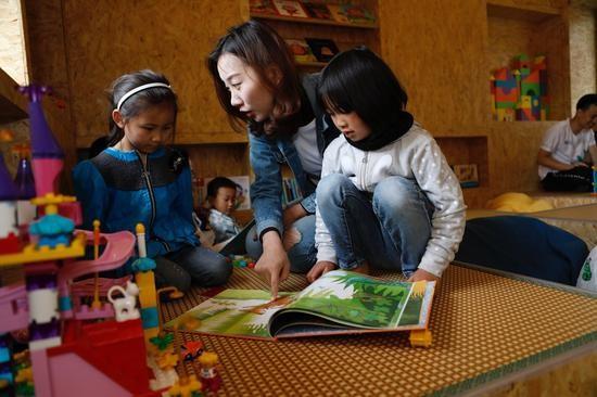 志愿者与学生在童趣园里共读绘本