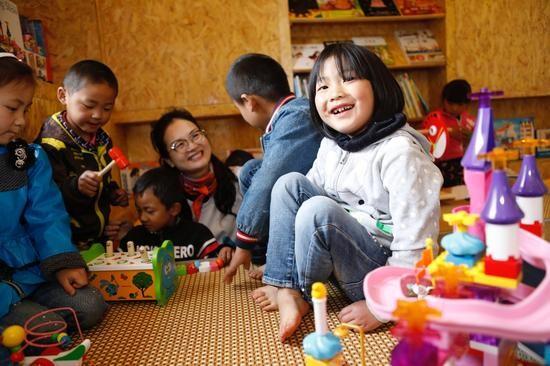 志愿者陪伴学生在童趣园里玩耍