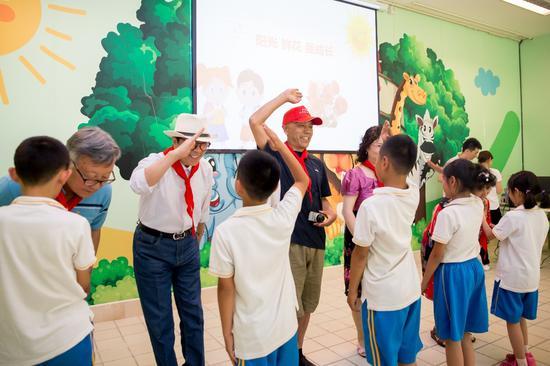 孩子们为老年志愿者戴上红领巾