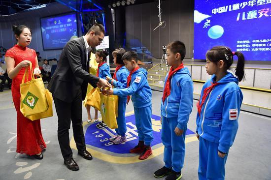 北京绿创公益基金会秘书长为学生代表赠送儿童道路安全科普手册及交通提示模型
