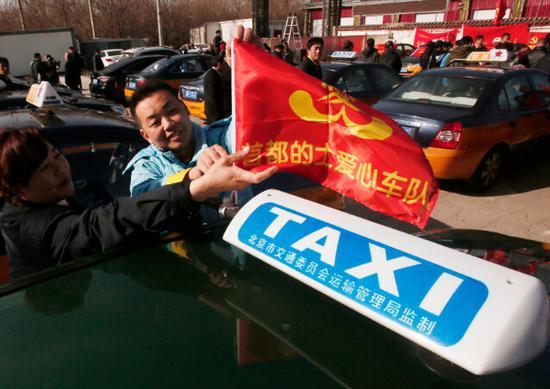 的哥的姐拜大年·温暖回家路,中国石油加油站员工为参与车辆插上活动旗帜。