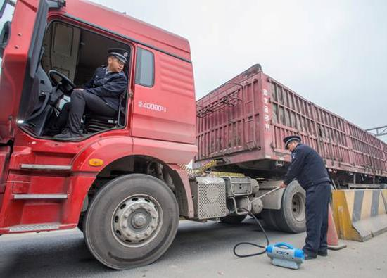 22日,琉璃河综合检查站加大重型柴油车检查力度,北京房山区环保局生态环境执法支队第六大队在检测尾气。(房山区环保局供图)
