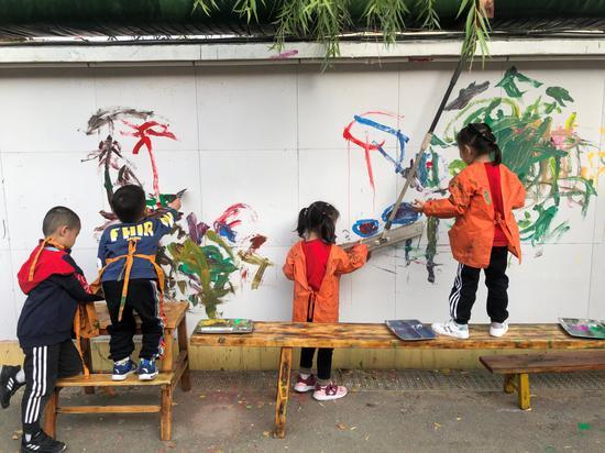 幼儿园的孩子阐扬缔造力建造墙绘