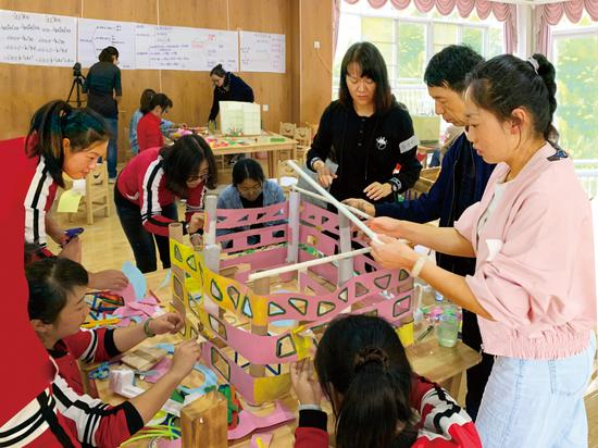 """幼儿教员在云南到场STEAM任务坊休会勾当""""建构幼儿园""""。"""