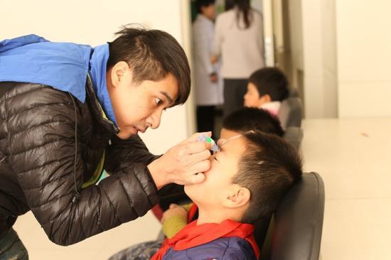 志愿者现场为小朋友们滴人工泪液为视力筛查做准备