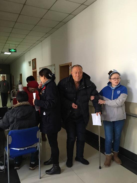 捷成志愿者搀扶老人进行检查