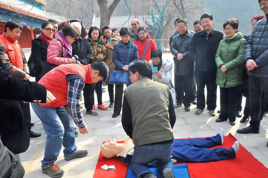 """门头沟区红十字会救援队给学员们详细生动地讲解了心肺复苏、外伤包扎等应急救护常识,将""""人人学急救,急救为人人""""的精神传递给学员们。学员们认真学习应急救援常识,踊跃进行实际操作,还不断向救护队员提出问题。救护队员对学员们的动作规范进行了指导,并就应急救护相关问题进行了解答。"""
