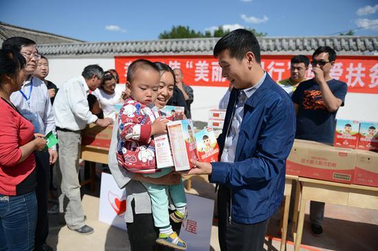 捐赠仪式后,张旭东秘书长在白石山村村委会操场上为贫困婴童家庭发放贝因美婴幼儿奶粉等食品物资
