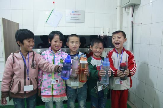 新地小学的孩子们簇拥在爱心水站前品尝甘甜的直饮水