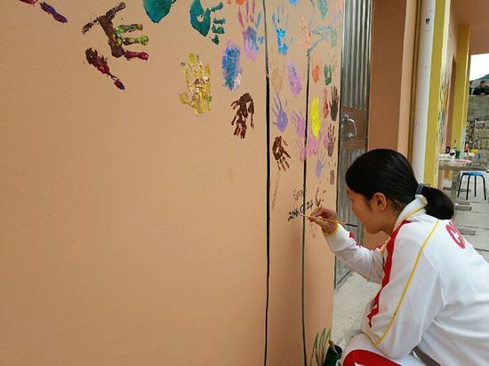 张雨涵画好梦想树,应学生邀请签下自己的名字