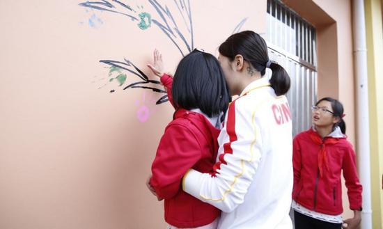张雨涵帮助小朋友印下自己的手印