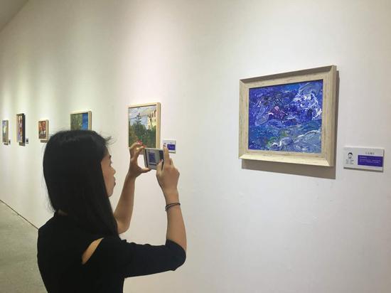 """观众参观""""寻找中国的梵高""""特殊艺术家画展"""