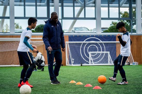 前托特纳姆热刺足球俱乐部队长和英格兰国家队员莱德利·金给小球员进行足球技能培训