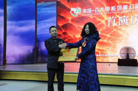珠海市慈善总会副会长王棱汸向邓春晖(左)颁发传眉心秀慈善基金成立牌匾