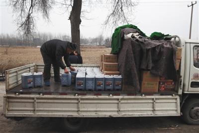1月16日,天津独流镇西北民主街附近一假醋制造窝点,执法人员雇请的工人将涉假调料和设备装上卡车。新京报记者 大路 摄
