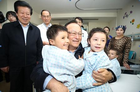 雪克来提·扎克尔与患儿亲切合影 摄影:白姜江