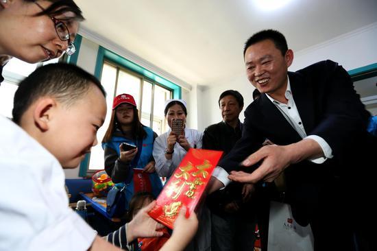 人人公益网董事长贾杰向贫困家庭脑瘫儿童发放慰问金